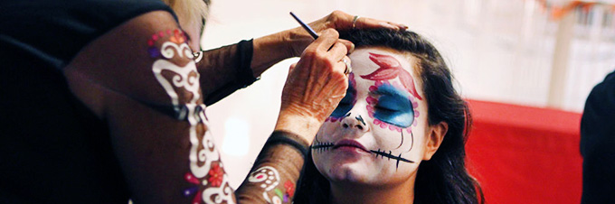 Student painting face designs during Dia de los Muertos. Photo credit: Anna Gallagher