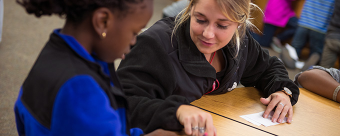Student working with child in after school program